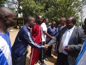 Migori Deputy Governor Mwita Mahanga (In suit) congratulates Nick Oluoch, a coach